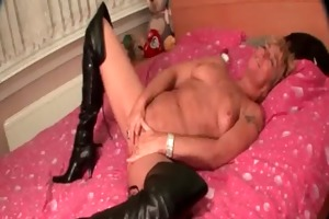 older in leather boots doing herself in sofa